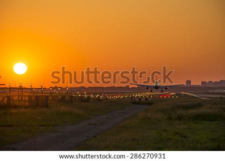 Small plane landing at dusk - stock photo