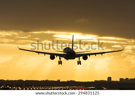 Small plane landing during sunrise. - stock photo