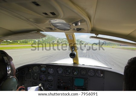 Small plane pilot flying and landing over tropical island in Caribbean - stock photo