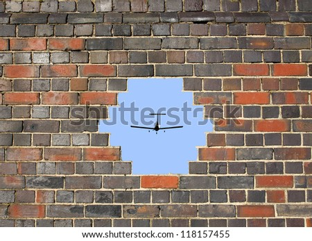 Small plane through a hole in a brick wall background - stock photo