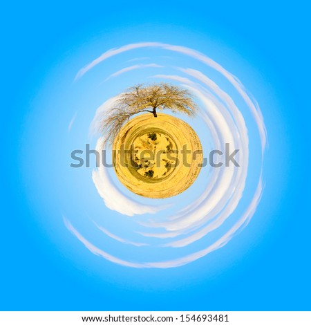 Small planet with a desert, mountains, clouds and lonely tree - stock photo