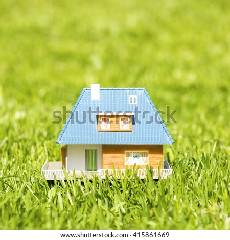 small plastic house on green grass - stock photo