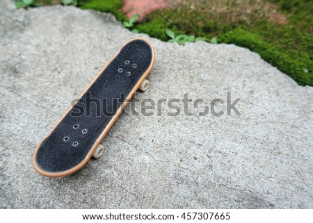 small plastic skate on concrete with tiny plants environment background.
