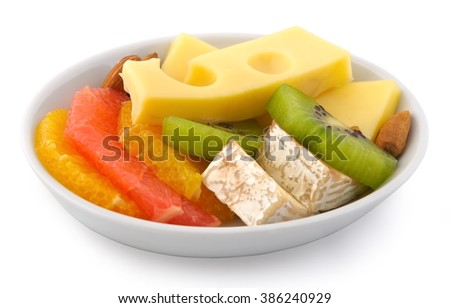 Small plate of inflight meal, various cheeses, kiwi, grapefruit and nuts on a white background - stock photo