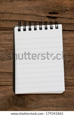 Small pocket sized notepad on a rustic wooden background with blank space for inserting your own message or note.