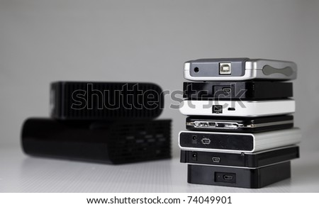 Small portable hard drives in stack.