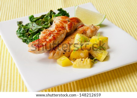Small portion of roasted chicken breast with saute kale leafs and squash vegetables, garnish with lime. selective focus, shallow dof - stock photo