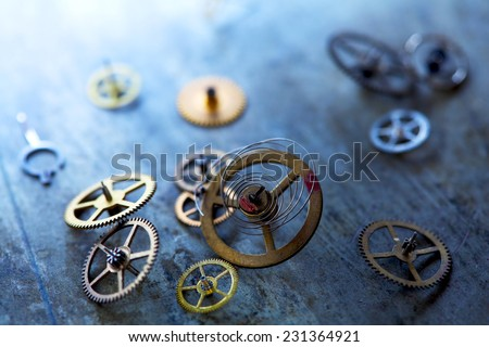 small precession gears of clock scattered on a grungy metal surface.  - stock photo