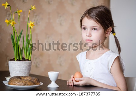 Small preschooler girl sitting at the table holding Easter egg in her hands - stock photo