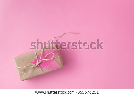 Small present in recycled craft paper on pink background - stock photo