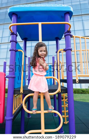 Small pretty girl climbing on a playground - stock photo