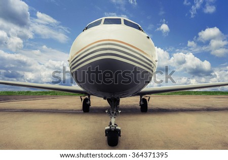 Small private aircraft at the airport parking, front view, closeup - stock photo