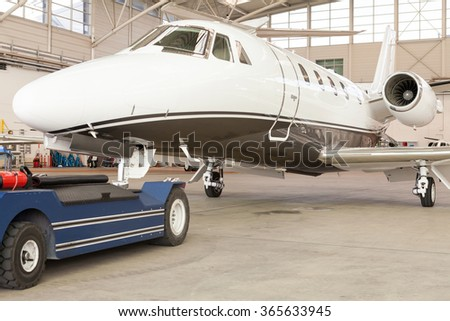 Small private corporate jet with green, red and white markings parked in a hangar at an airport, close up angled view of the nose and fuselage in an aviation, transport and travel concept - stock photo