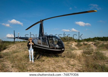 Small private helicopter landed on the beach dunes - stock photo