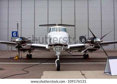 small private propeller aircraft with two engine on the background of a hangar  - stock photo