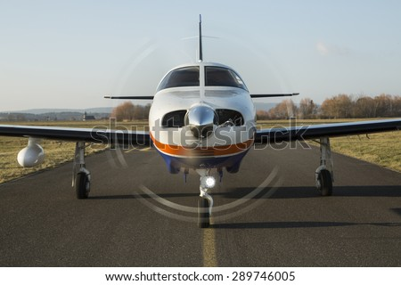 Small private single-engine piston aircraft on runway, front view - stock photo