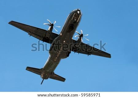 small propeller cargo aircraft on landing approach - stock photo