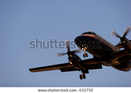 Small propeller plane approaching an airfield in the afternoon light - stock photo