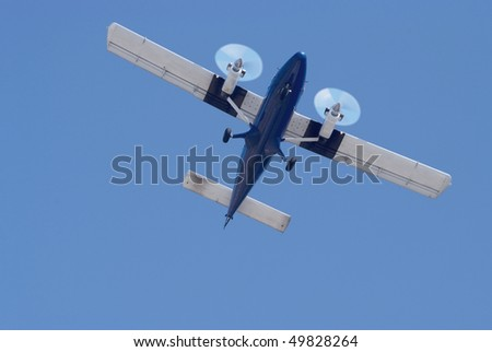 small propeller twin engine airplane on a blue sky background - stock photo
