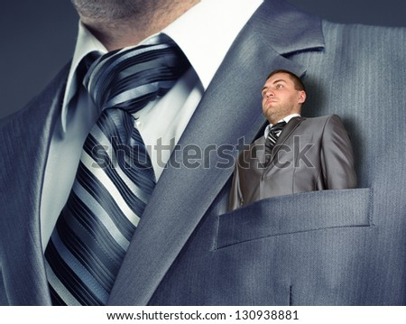 Small puppet businessman in suit pocket - stock photo
