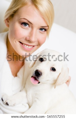 Small puppy sitting on the hands of woman