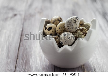 Small quail eggs in a dish on a wooden table - stock photo
