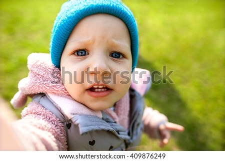 small rebenou makes selfie. Walking in the park on the green grass - stock photo