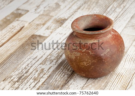 small red and brown clay plant pot (mass produced planter) with rough, grunge finish,  on white wood background - stock photo