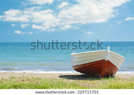 Small red boat lying at shore - stock photo