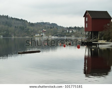 small red building on stilts on coastline in norway with forest and houses in background - stock photo