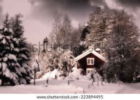 small red cottage surrounded by snowy winter landscape, at dusk, typica scenery from Sweden - stock photo