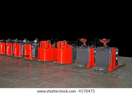 Small red fork lifter truck in line - stock photo