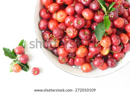 Small red fruit . Brazilian Acerola Fruit . small cherry in a bowl on wooden background.