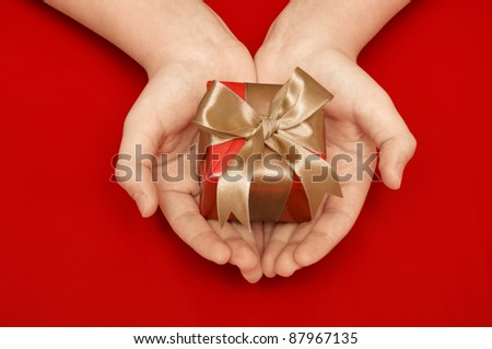 Small red gift in a female hand over red background - stock photo