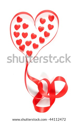 Small red hearts and ribbon in heart shape on white background