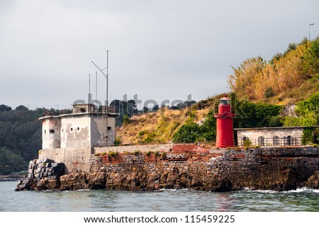 small red lighthouse on a stony shore in italy - stock photo