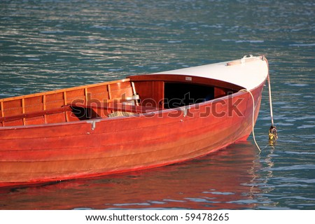 Small red wood boat floating on the water by sunset