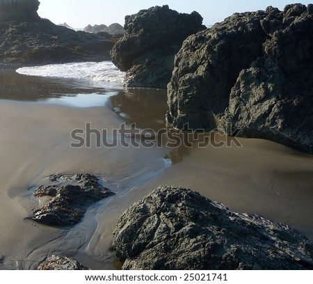 Small riptide moves along the sand on a rocky beach in Oregon - stock photo