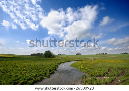 Small river, farmland and blue and cloudy sky.