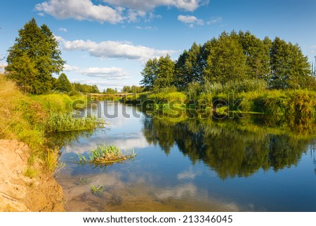 small river on green field on background sky