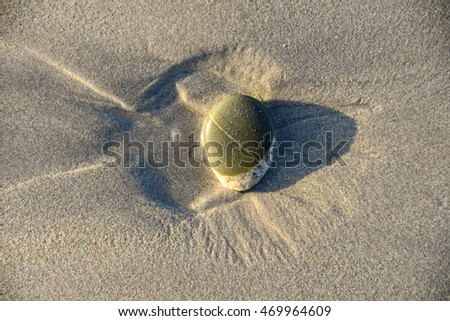 small rock on beach sand creating a small pool of water and a delta fan  pattern