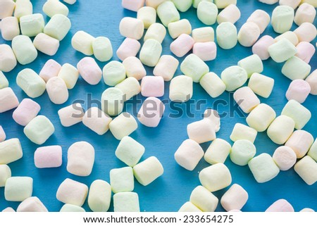 Small round multicolor marshmallows on blue backgrouns.
