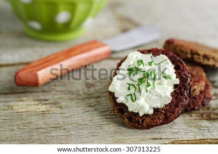 Small round rye toasts with cream cheese and dill - stock photo