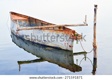 Small rowboat in the lake and clear reflection in the water - stock photo
