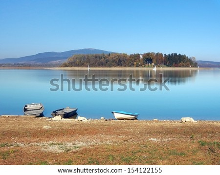 Small rowing boats on shore with Slanica Island, also called Island of art. Slanica Island is located in Orava reservoir. Slanica Island hosts permanent expositions showcasing traditional folk art.