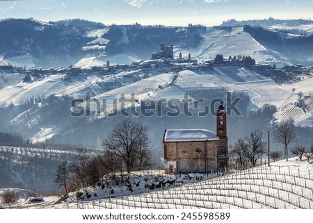 Small rural church and vineyards covered with snow in Piedmont, Northern Italy. - stock photo