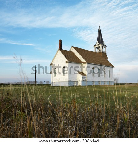 Small rural church in field with chipped wood siding. - stock photo