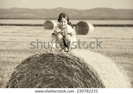 small rural girl on the straw after harvest field with straw bales on sepia brown color - stock photo