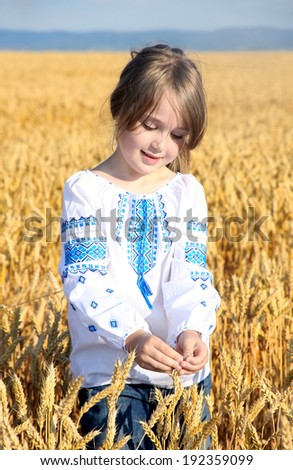 small rural girl on wheat field - stock photo