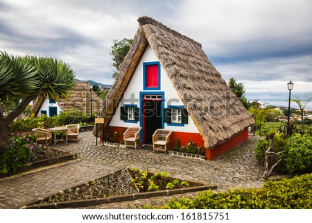 Small rural house with a triangular thatched roof. The red door and small windows with shutters. Santana city in Madeira island,Portugal - stock photo